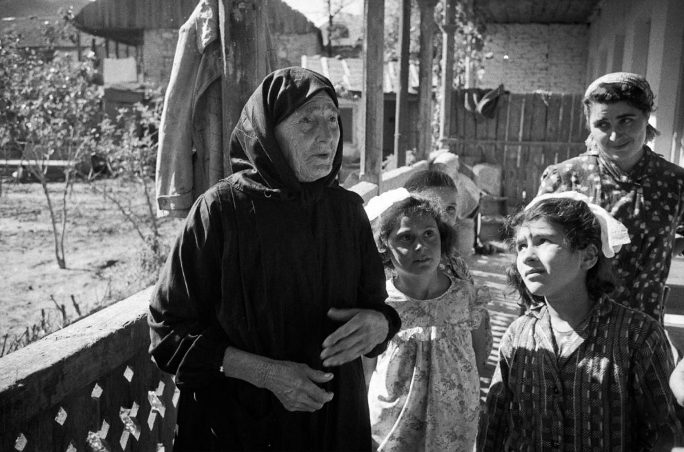 Пожилая женщина в национальное одежде с дочерью и внучками
