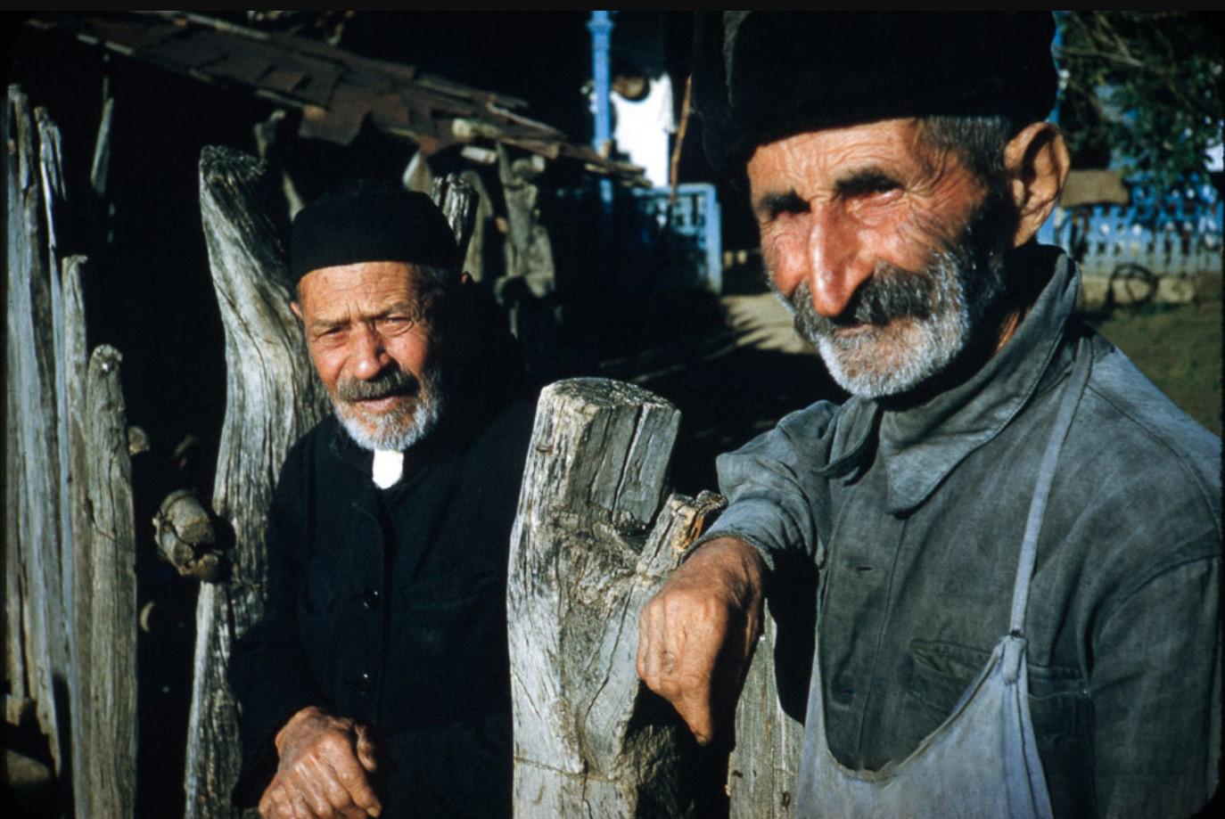 Двое пожилых мужчин позируют у ограды дома