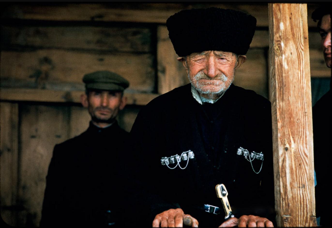 Пожилой мужчина в национальном костюме чоха и кинжалом кама с сыновьями
