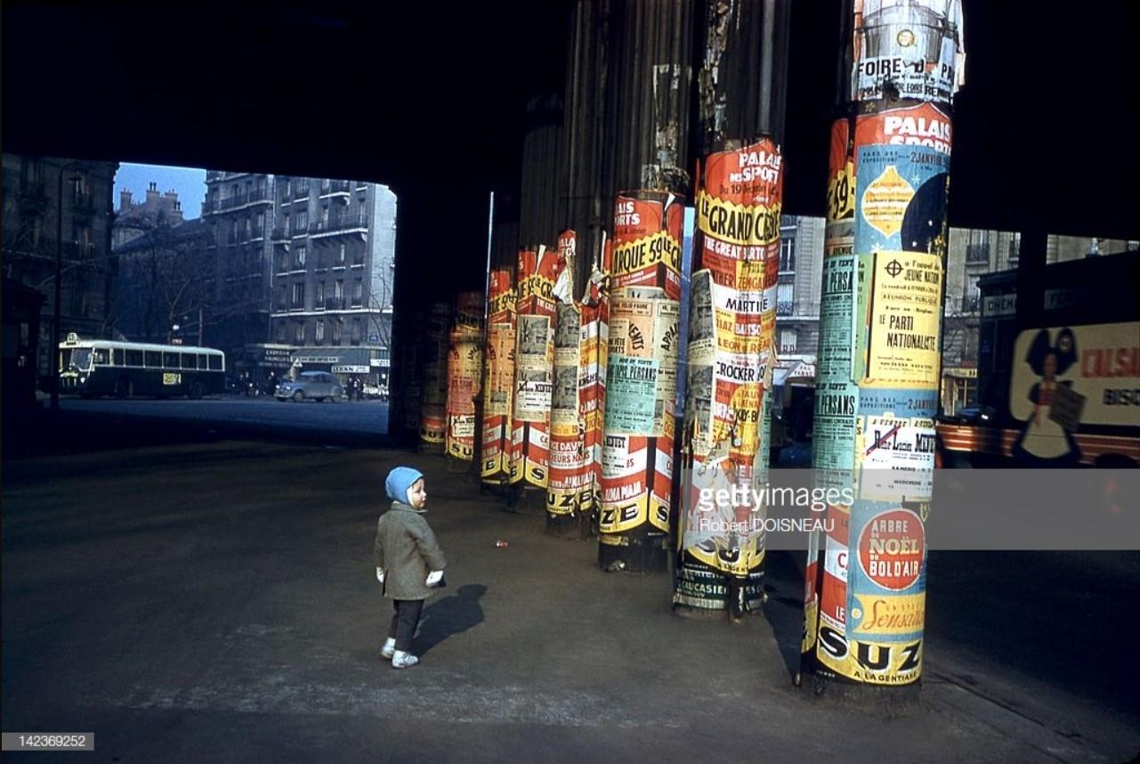 1959. Маленькая девочка, идущая под мостом, столбы которого полностью покрыты рекламными плакатами, Париж