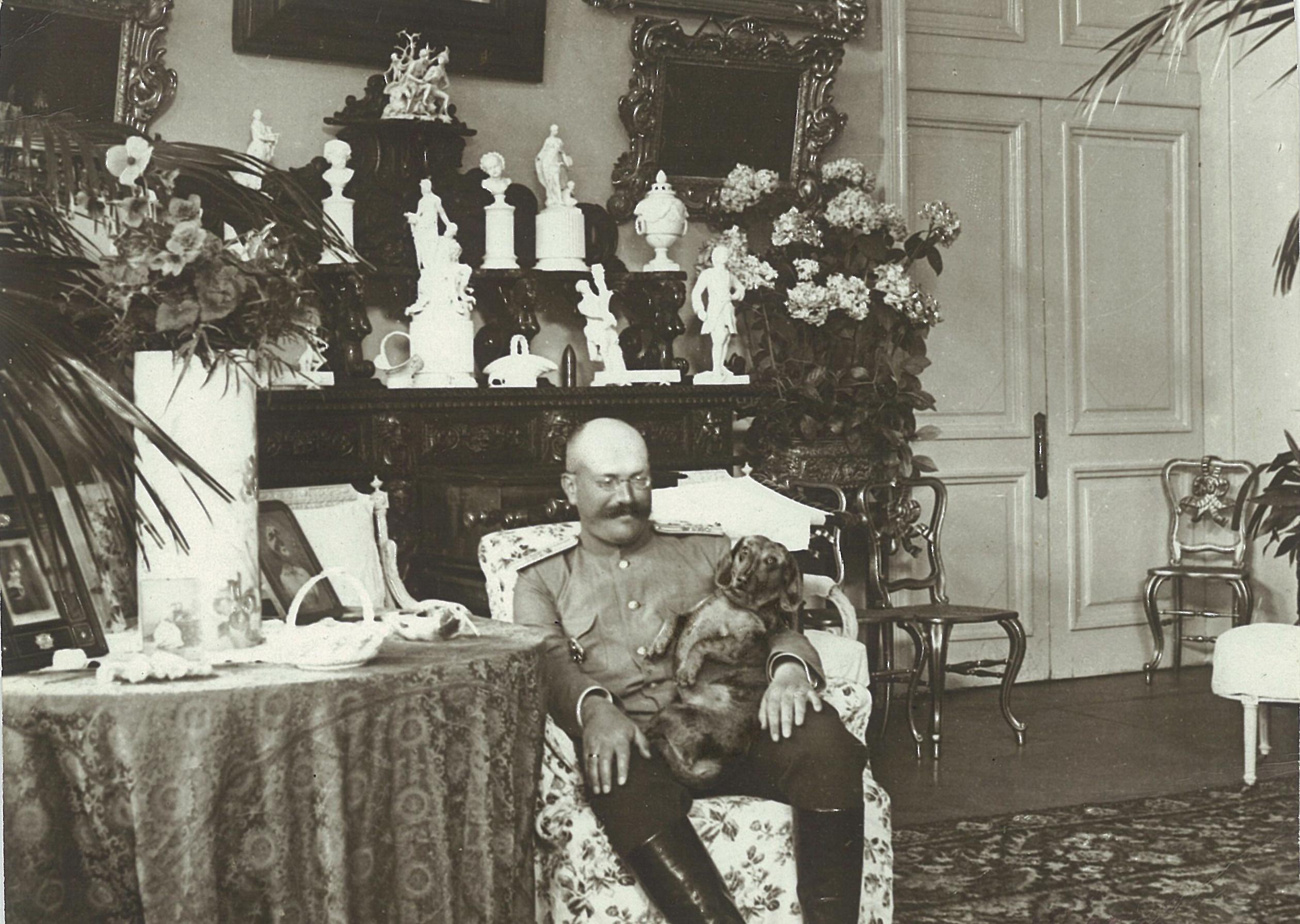 В.П.Всеволожский с собакой в одном из залов усадебного дома в Рябово (на фоне коллекции фарфора),