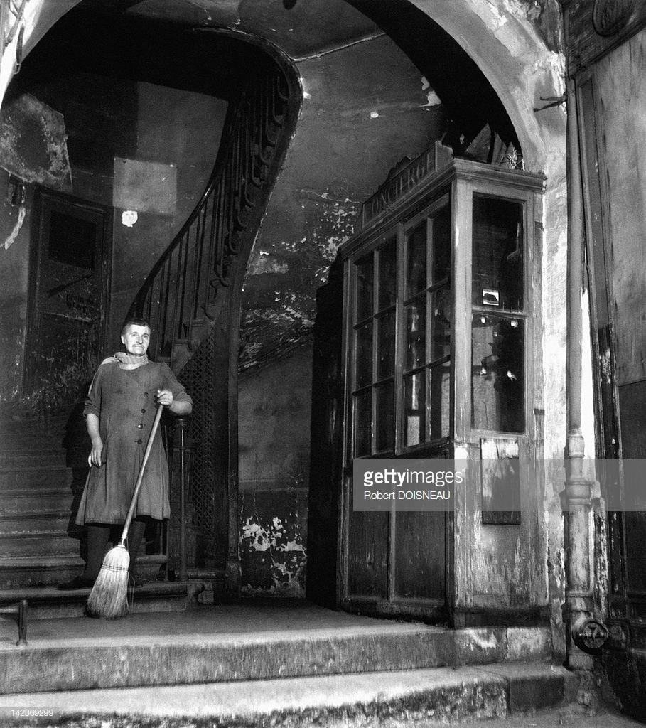 1946. Консьерж с метлой, убирающей вход в здание