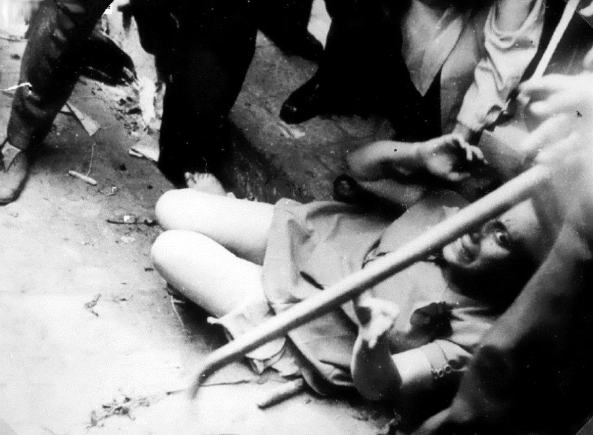 Еврейка сидит у ног бойцов «Украинской народной милиции» ОУН(б) во время погромов во Львове. 30 июня-2 июля 1941