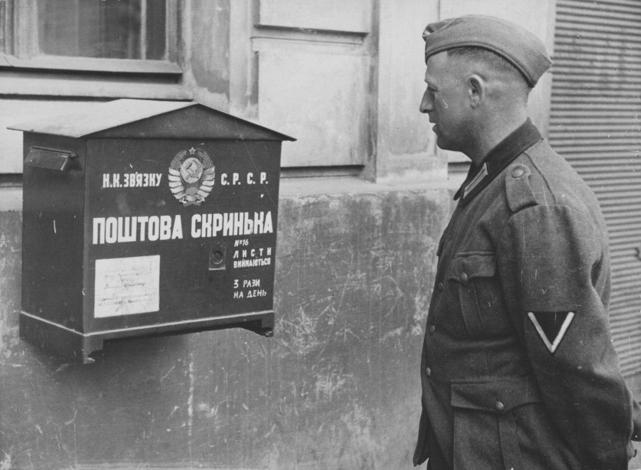 Немецкий солдат смотрит на почтовый ящик на стене дома во Львове, июнь - июль 1941 года.