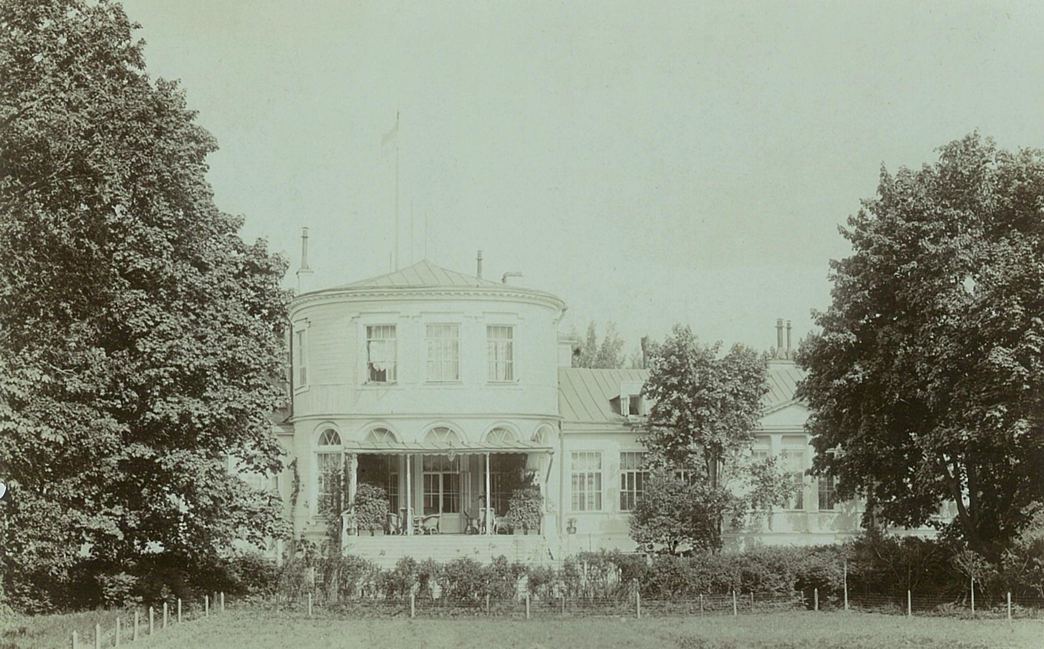 Садовый фасад усадебного дома с сетчатой оградой по периметру луга