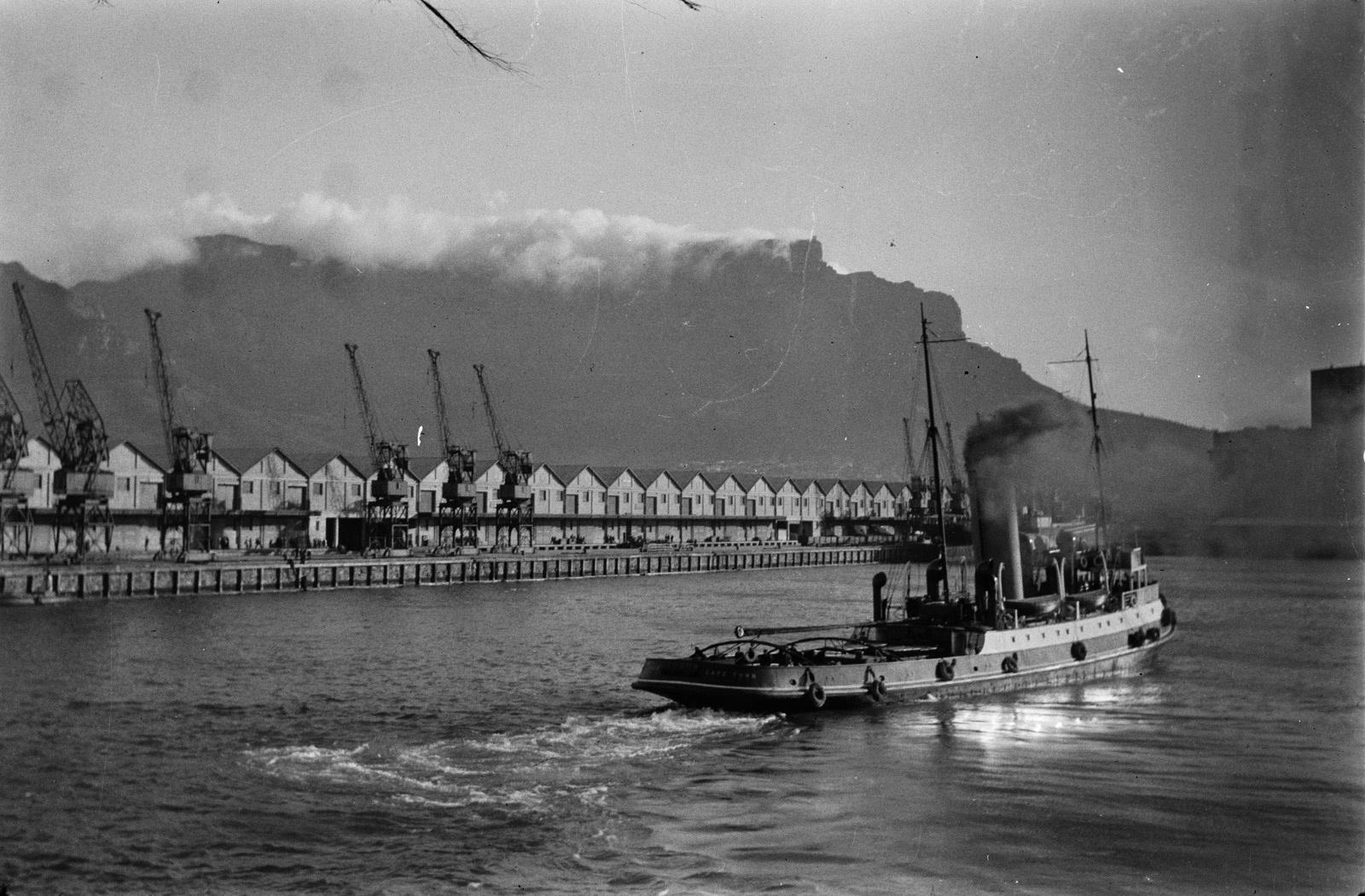 Кейптаун. Буксир в гавани Кейптауна. Слева - пристань. На заднем плане Столовая гора