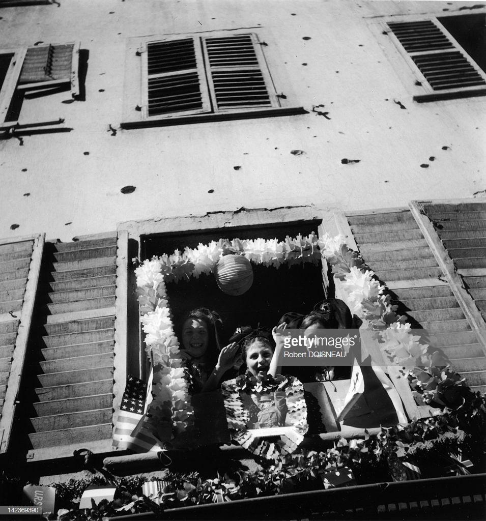 1945. Три девушки, одетые в национальные костюмы региона смотрят в окошно во время праздника «кремации трех деревьев», этот праздник проводится каждый год 30 июня в ознаменование основания города