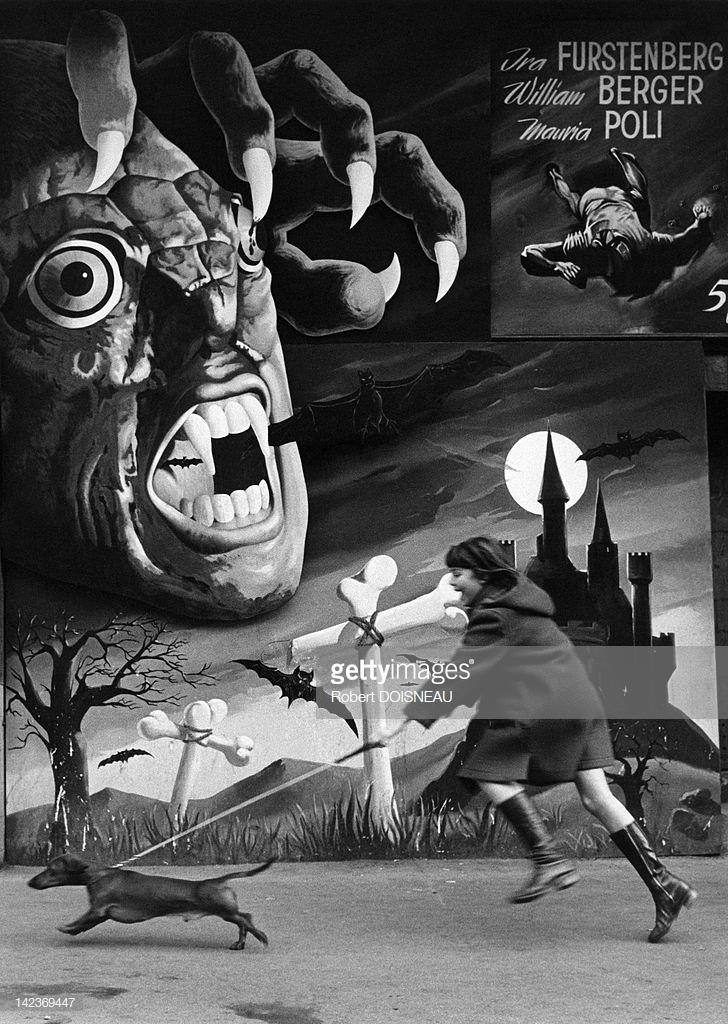 1972. Женщина и ее собака бегут перед огромным плакатом фильма ужасов Марио Бавы «5 кукол для августовской луны» на бульваре Клиши в октябре