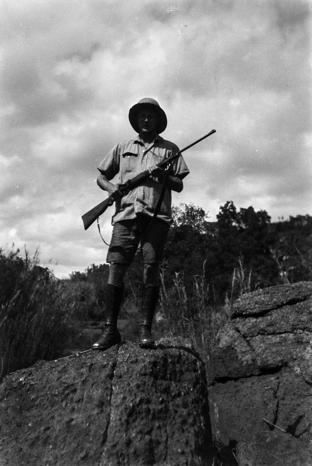 Между Капири Мпоши и рекой Лунсемфва. Портрет Эрнста Аккермана, стоящего на валуне и держащего винтовку