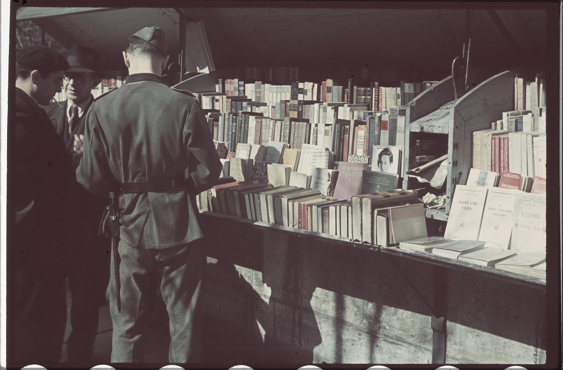 Немецкий солдат перелистывает книги в книжных развалах набережной Вольтера