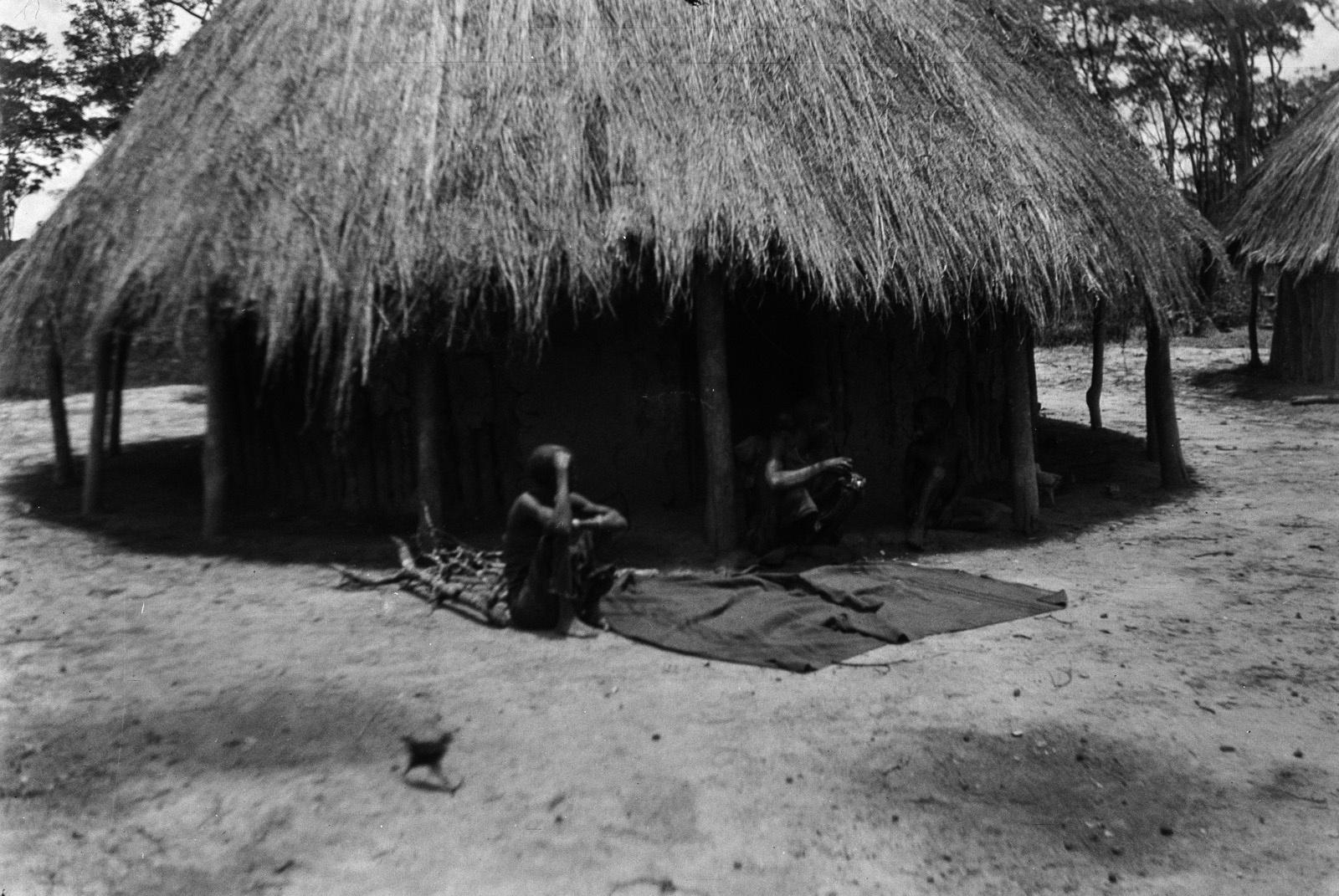 Между Капири Мпоши и рекой Лунсемфва. Деревня чеве. Хозяева возле своей хижины