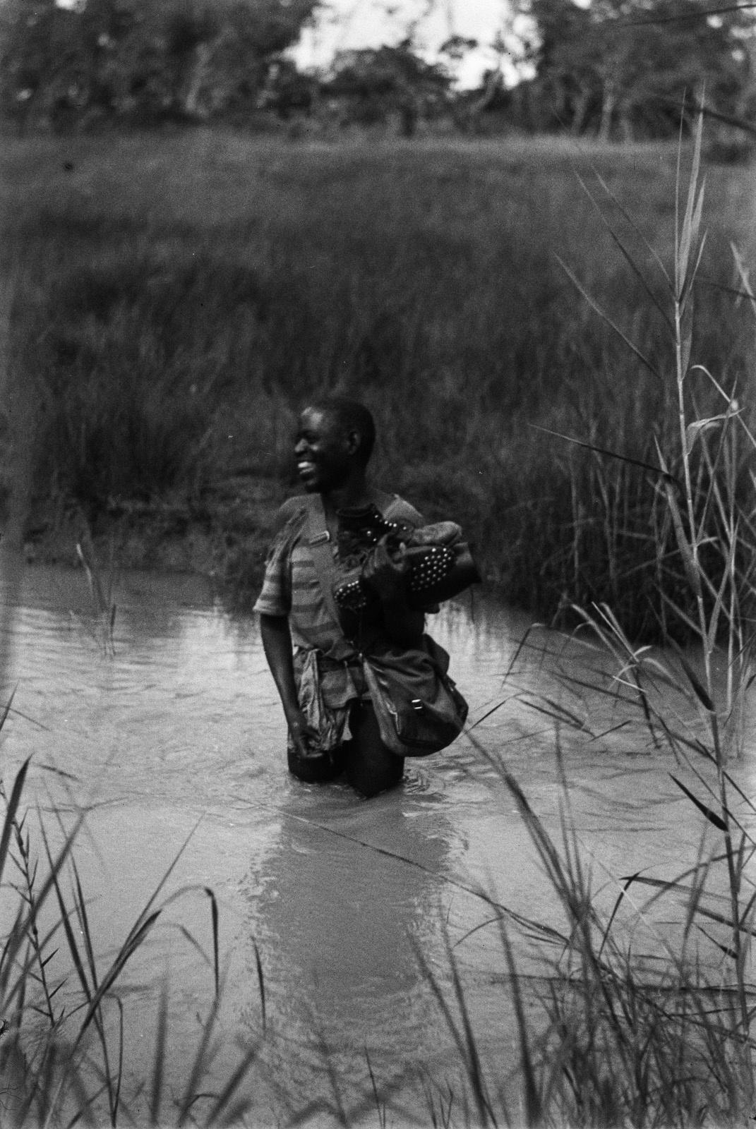 Между Капири Мпоши и рекой Лунсемфва. Человек пробирается сквозь ручей.