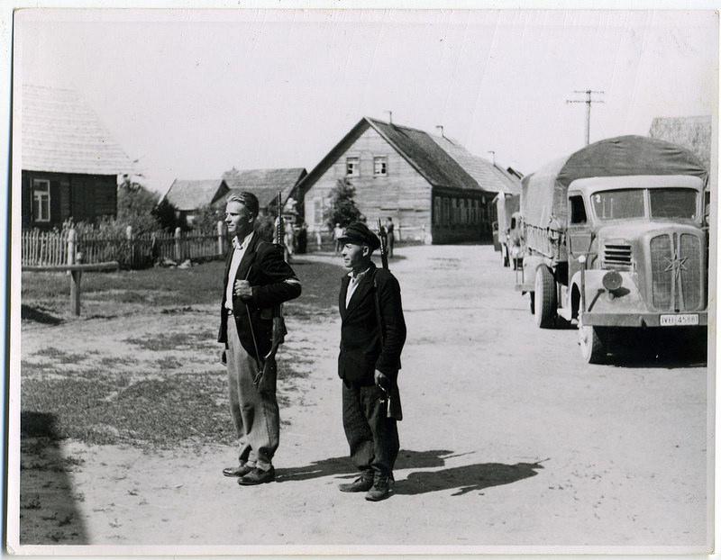 1941. 2 бойца самообороны с СВТ на фоне немецких грузовиков. Латвия. 8 июля