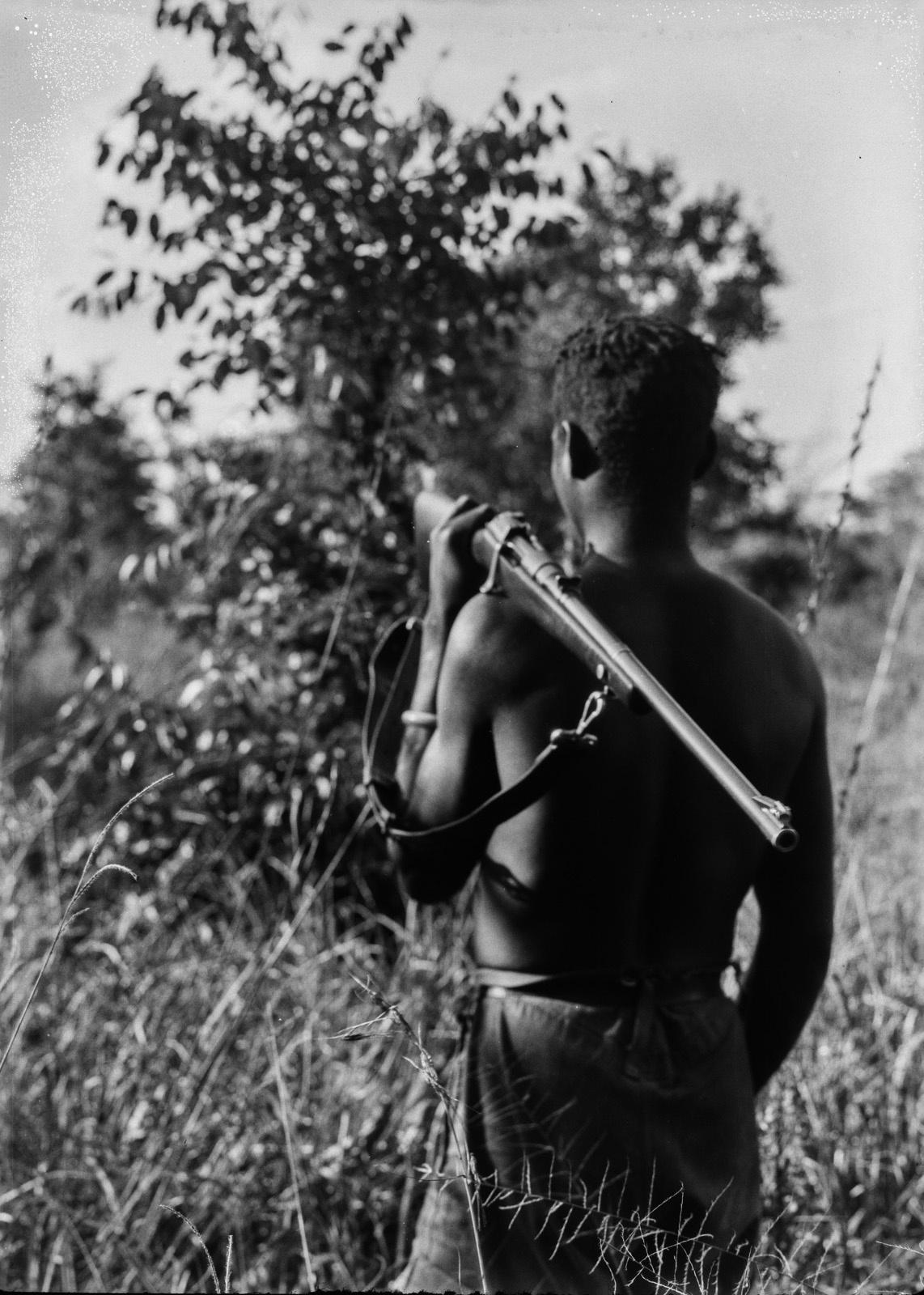 Касемпа. Абориген с ружьем в высокой траве