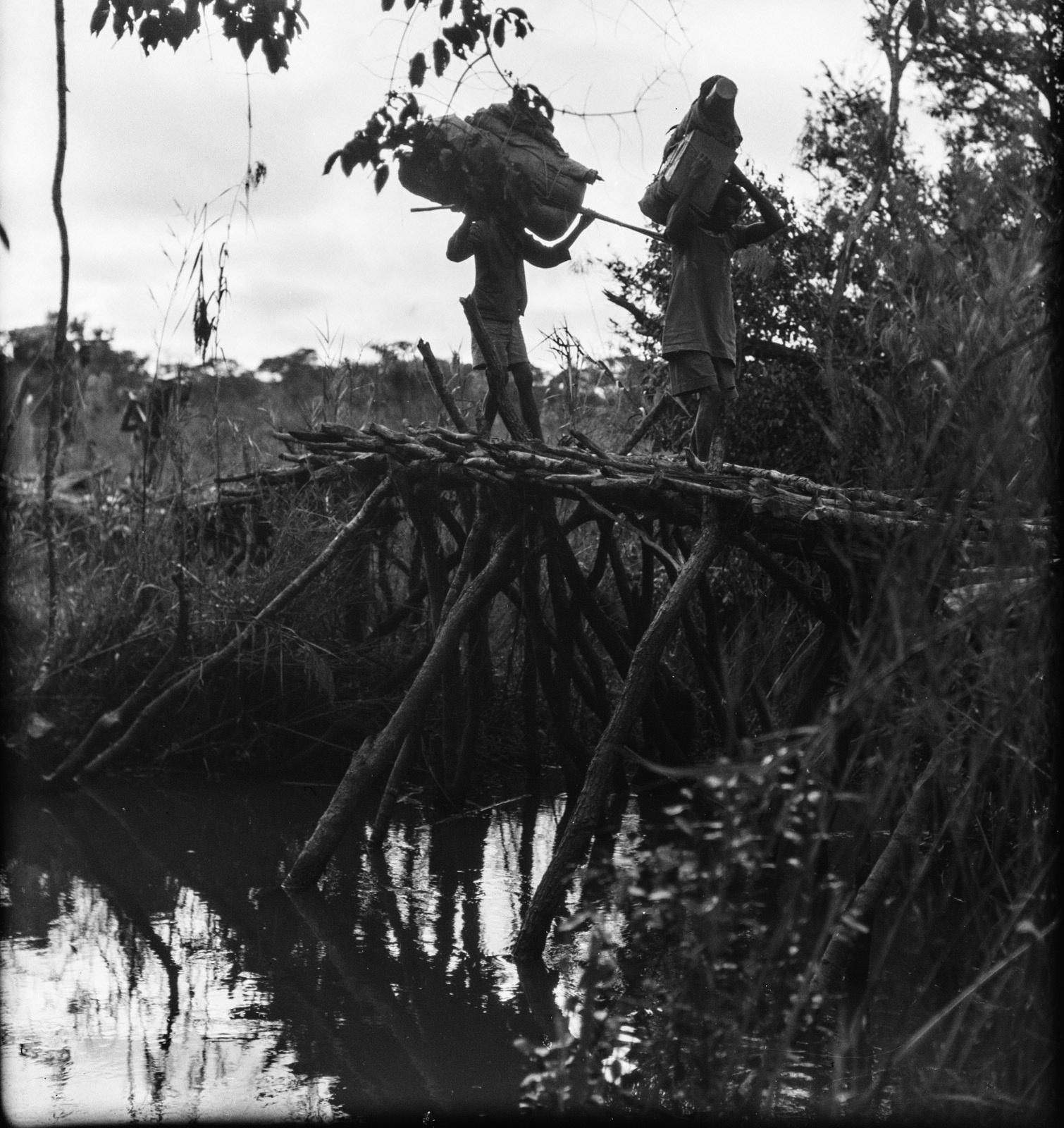 Канколонкола. Два носильщика используют почти разрушенный мост для перехода через ручей