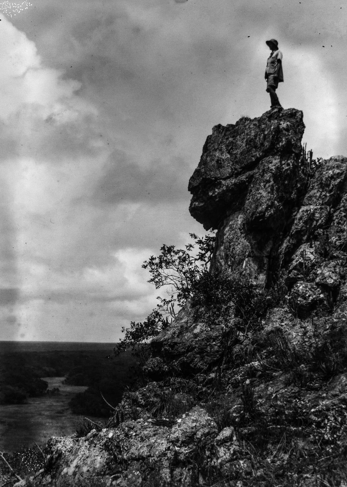 Капири-Мпоши.  Вид на скалу и лесистую равнину с ручьем.