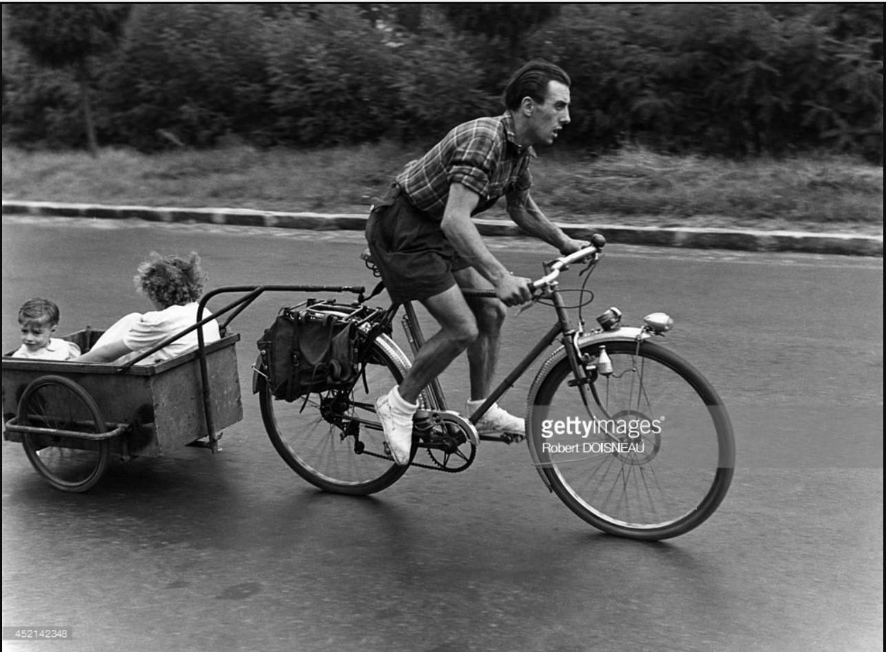 1950. Мужчина на велосипеде с детьми на прицепленной тележке