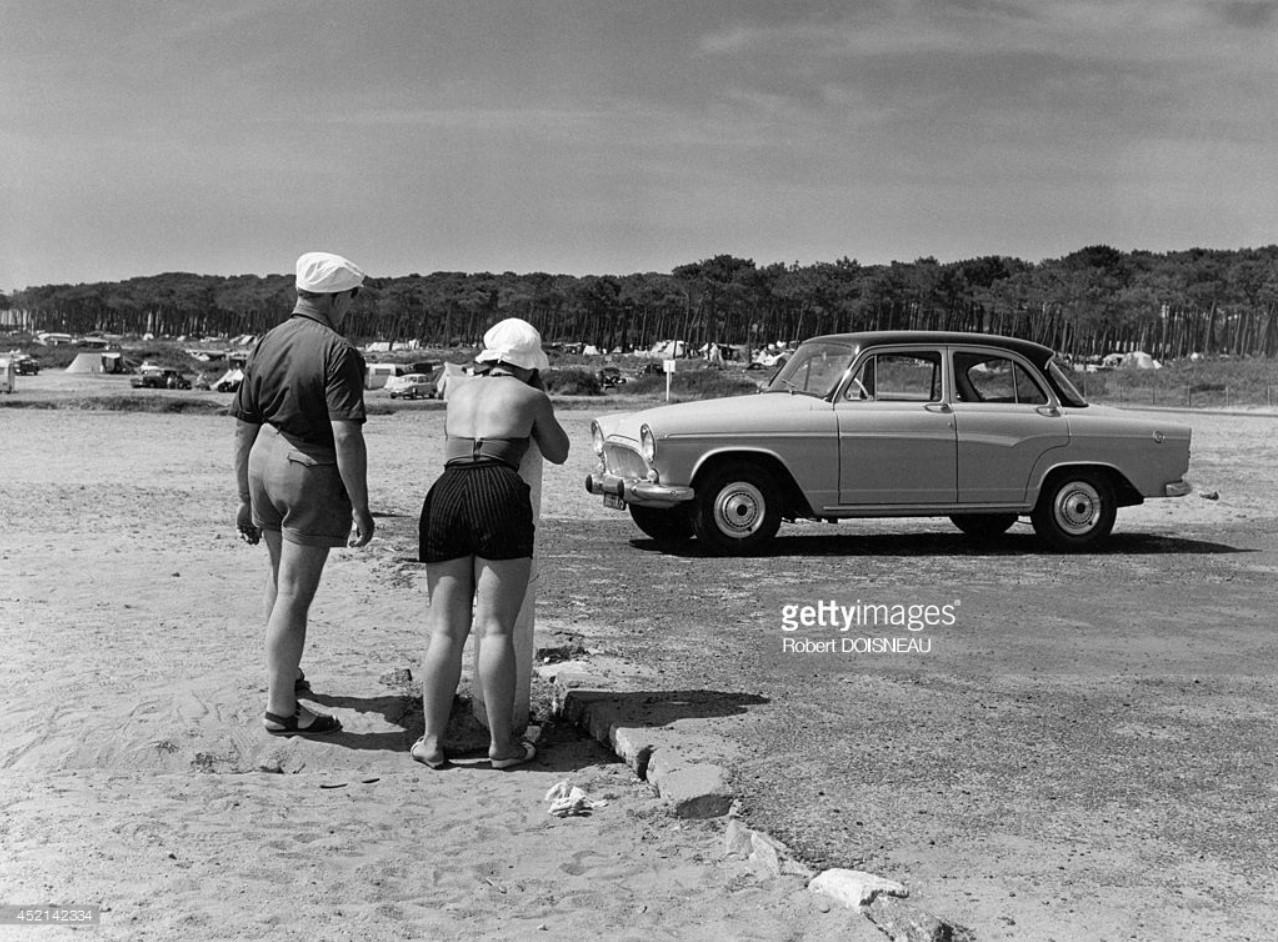 1960. Семейная пара фотографирует свой автомобиль во время отпуска
