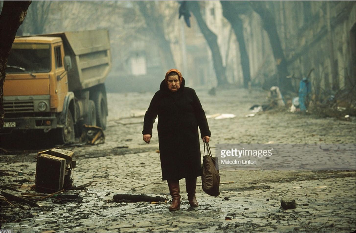 1991. 31 декабря. Тбилиси. Женщина идет по улице в зоне боевых действий возле здания парламента