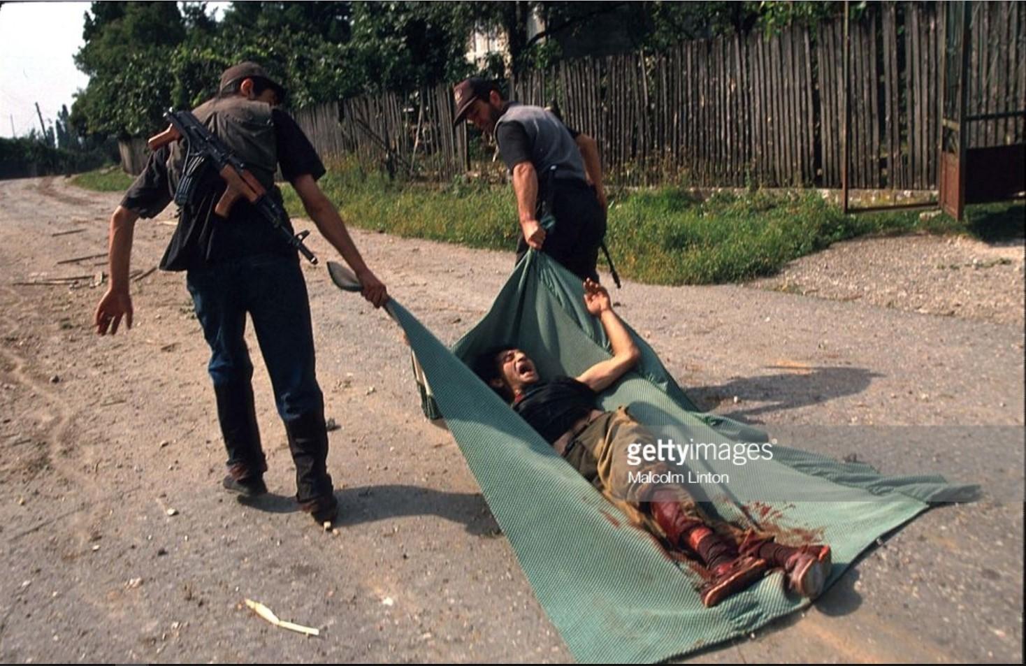 1993. 28 сентября. Сухуми. Два грузинских солдата тащат раненого товарища на одеялегода в Сухуми