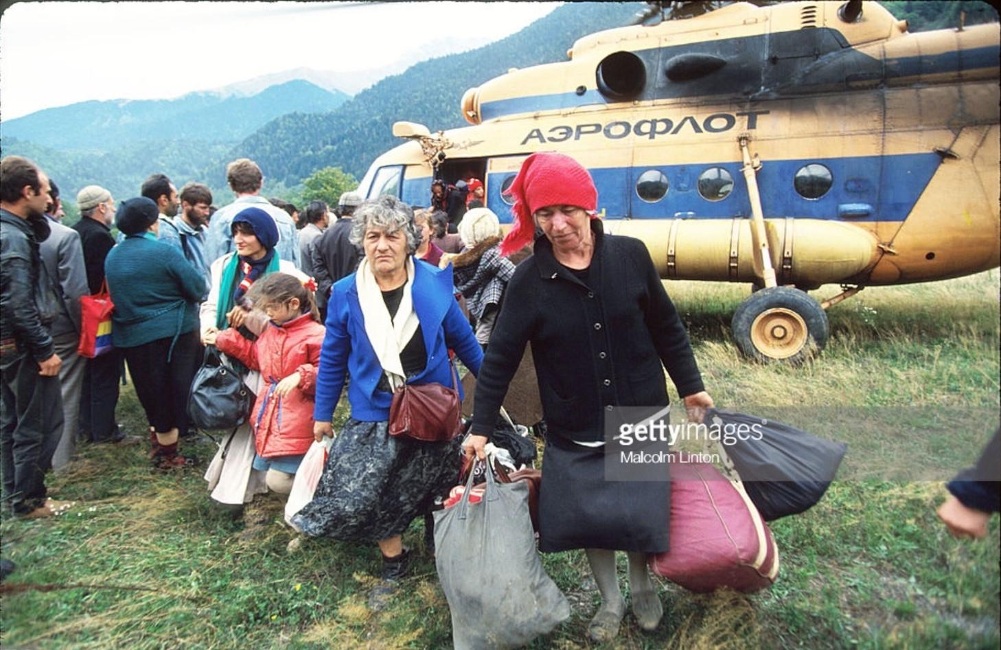 1993. 29 сентября. Окрестности Сухуми.  Беженцы переносят вещи, доставленные им вертолетом