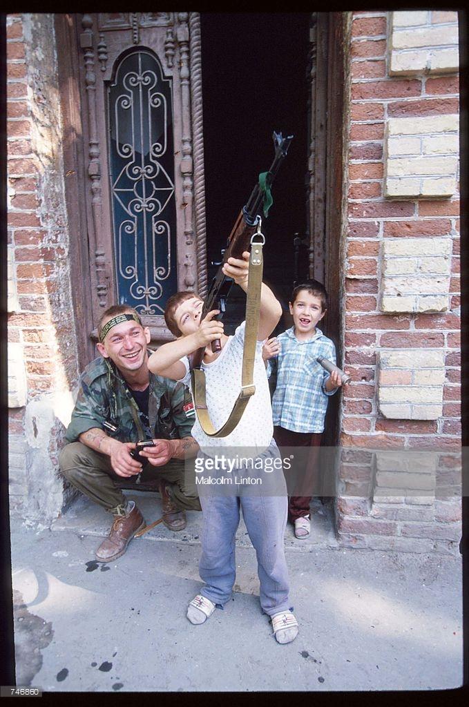 1993. 29 сентября. Сухуми. Ребенок играет с винтовкой под присмотром абхазского солдата