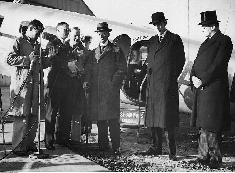 Премьер-министр Великобритании Невилл Чемберлен (в центре) в аэропорту Лондона перед отъездом в Германию. На фоне самолета вы также можете увидеть министра иностранных дел Великобритании Эдуарда Галифакса (второй справа)