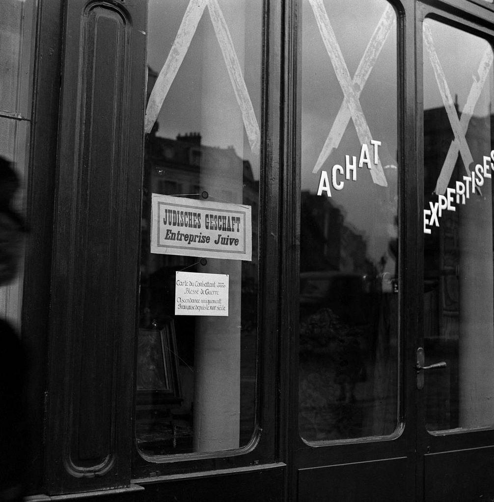 Плакаты (Judisches Geschäft, еврейский бизнес) на окнах принадлежащих евреям магазинов в оккупационной зоне