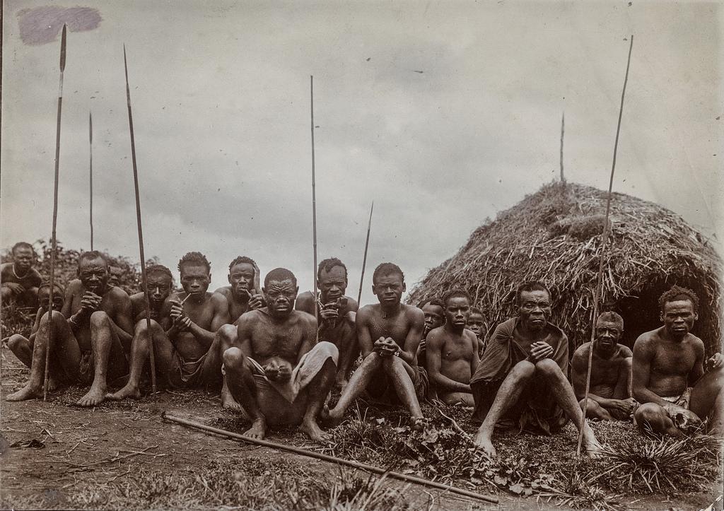 Групповой портрет с 16 мужчинами, сидящими перед хижиной