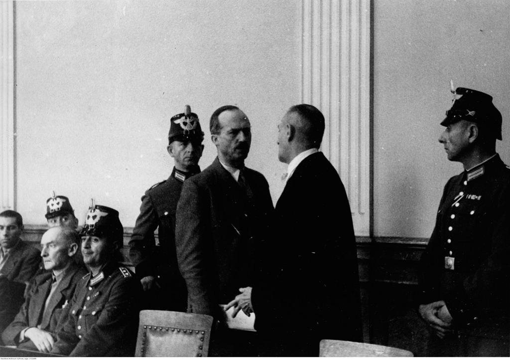 Обвиняемый Карл Пауль Эммануил фон Хазе разговаривает со своим адвокатом. Эрвин фон Витцлебен на скамье подсудимых.