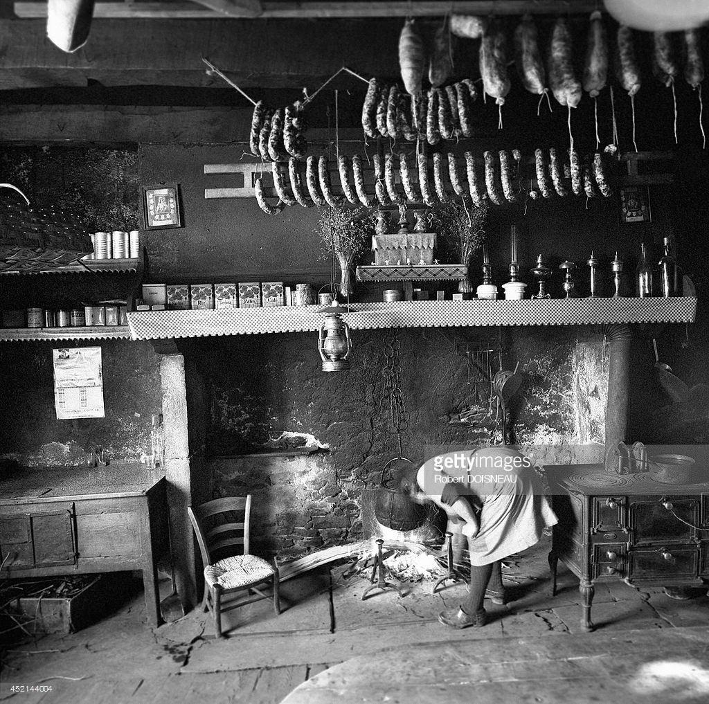 1964. Женщина перед камином в своем доме с большим количеством висящих свиных колбас. 30 марта