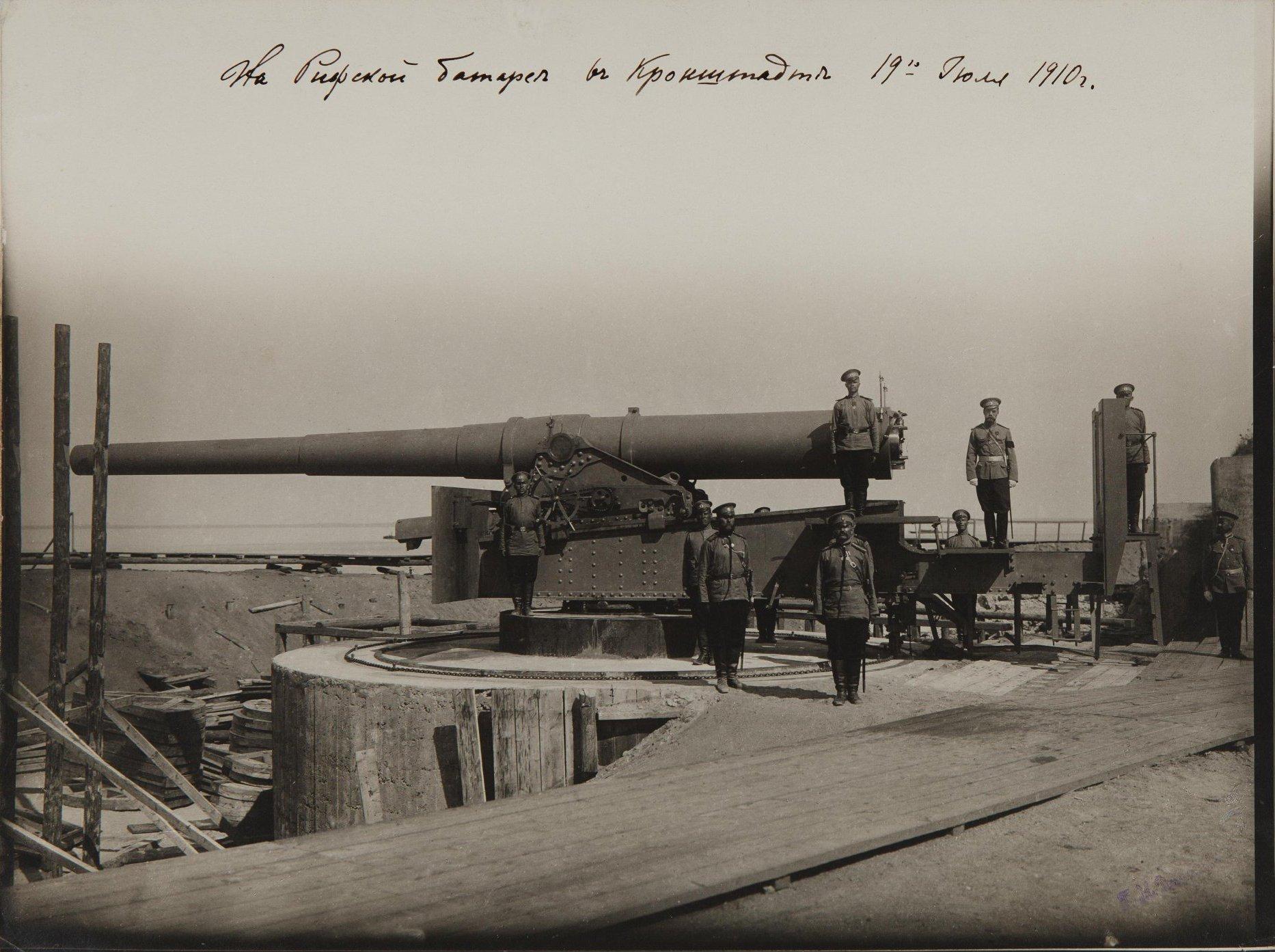 1910. Николай II в сопровождении военных у артиллерийского орудия на Рифской батарее. Кронштадт. 19 июля.jpg