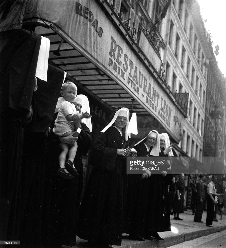 1944. Группа монахинь, одна с ребенком на руках во время освобождения Парижа.jpg