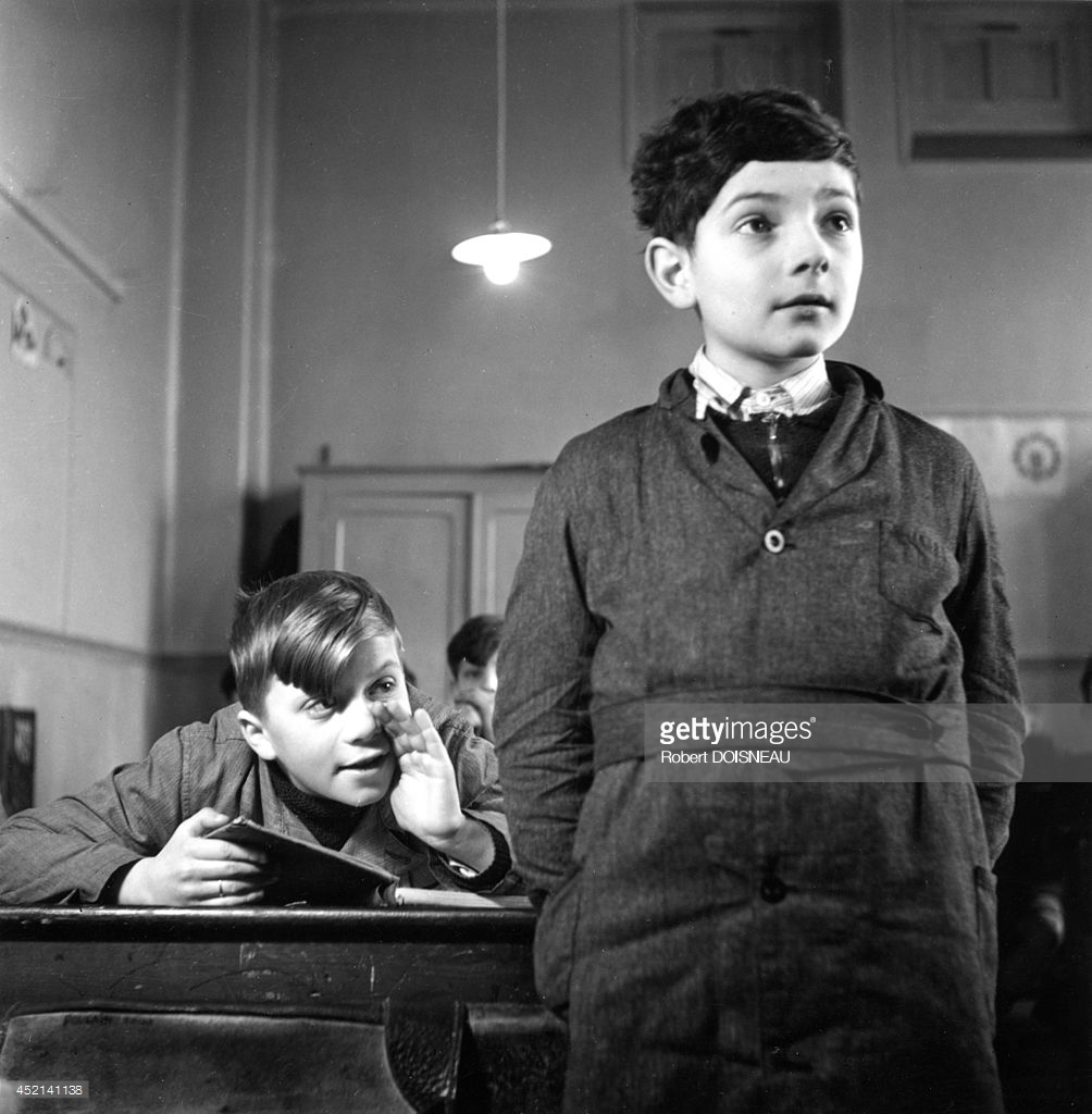 1945. Школьник помогает своему однокласснику во время занятий.jpg