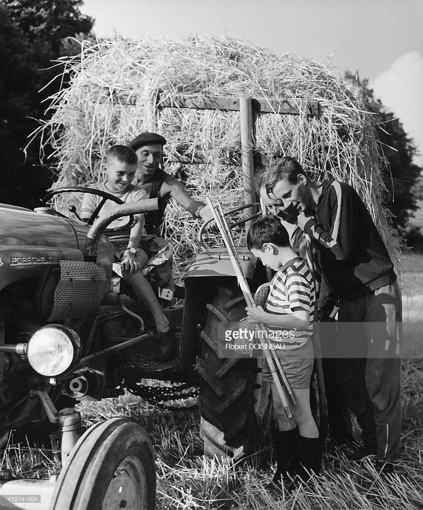 1964. Мальчик возвращается с рыбной ловли и показывает свою рыбу мужчине и мальчику, сидящему на тракторе. Коррез.jpg