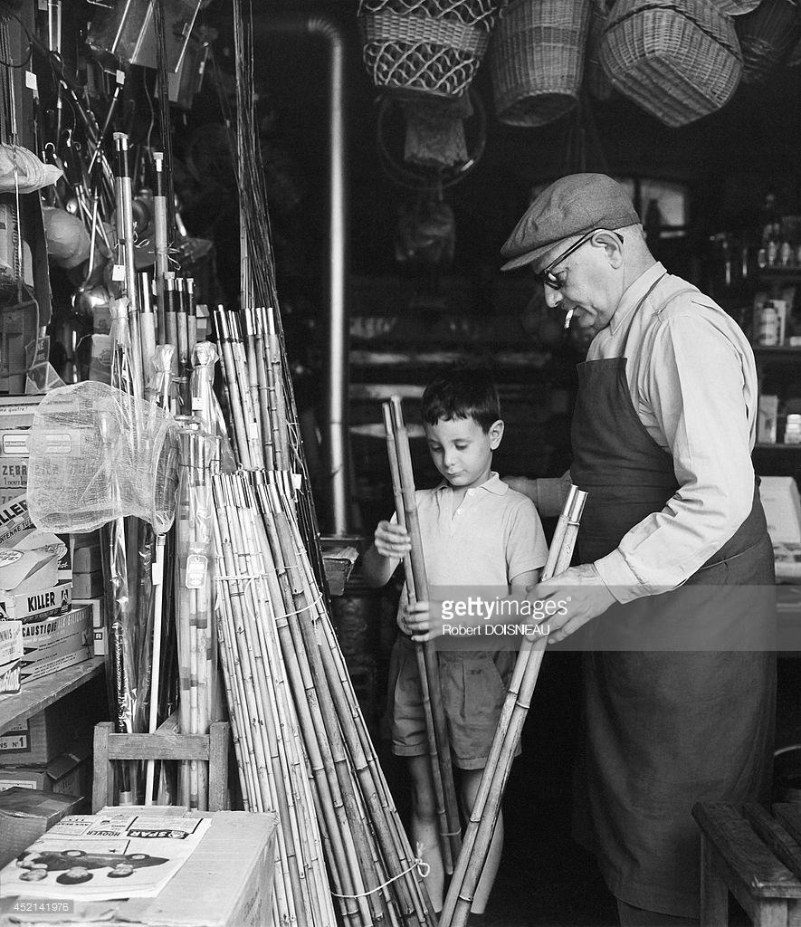 Мужчина и мальчик выбирают удочку в магазине рыболовных снастей.jpg