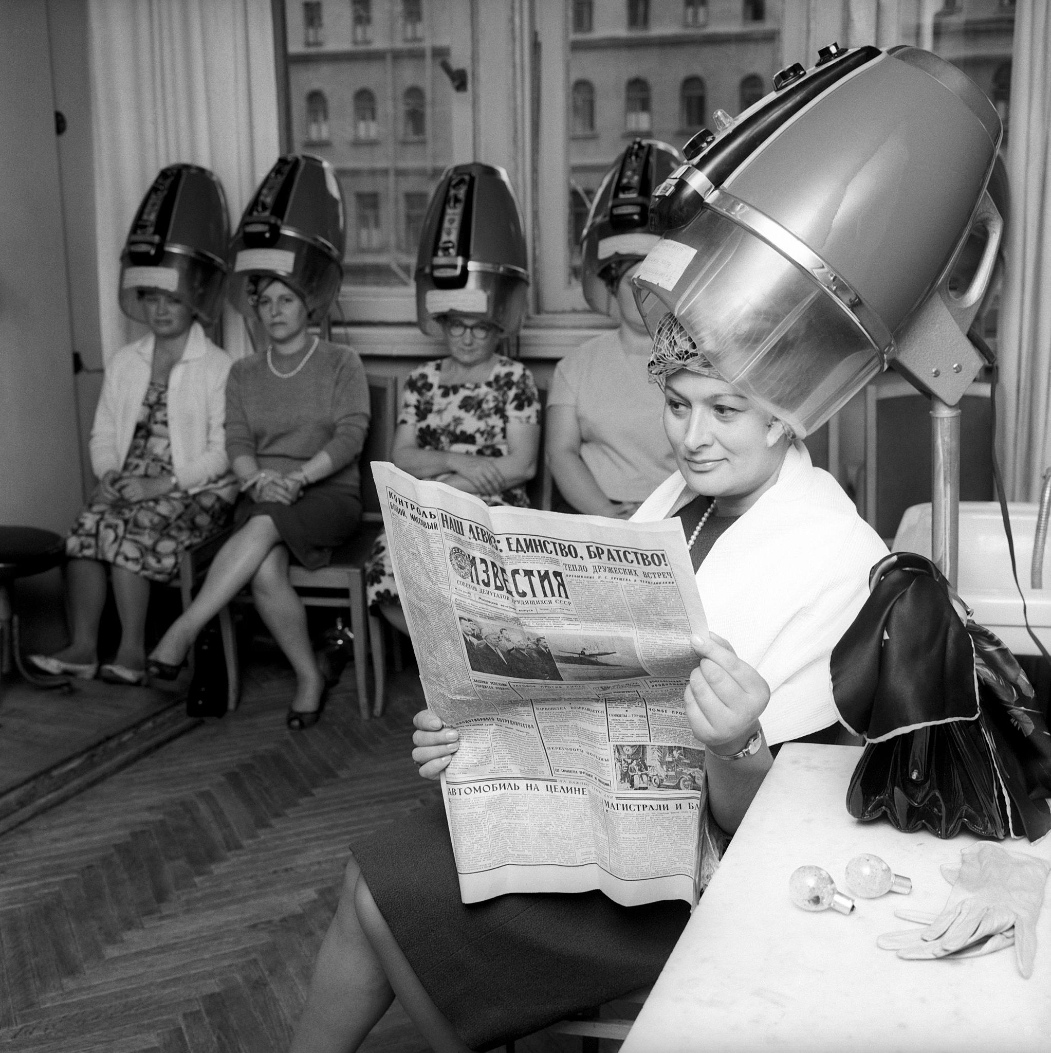 Волосы Эдды Винчензи устраиваются, прежде чем она выйдет на сцену; она читает российскую газету.png