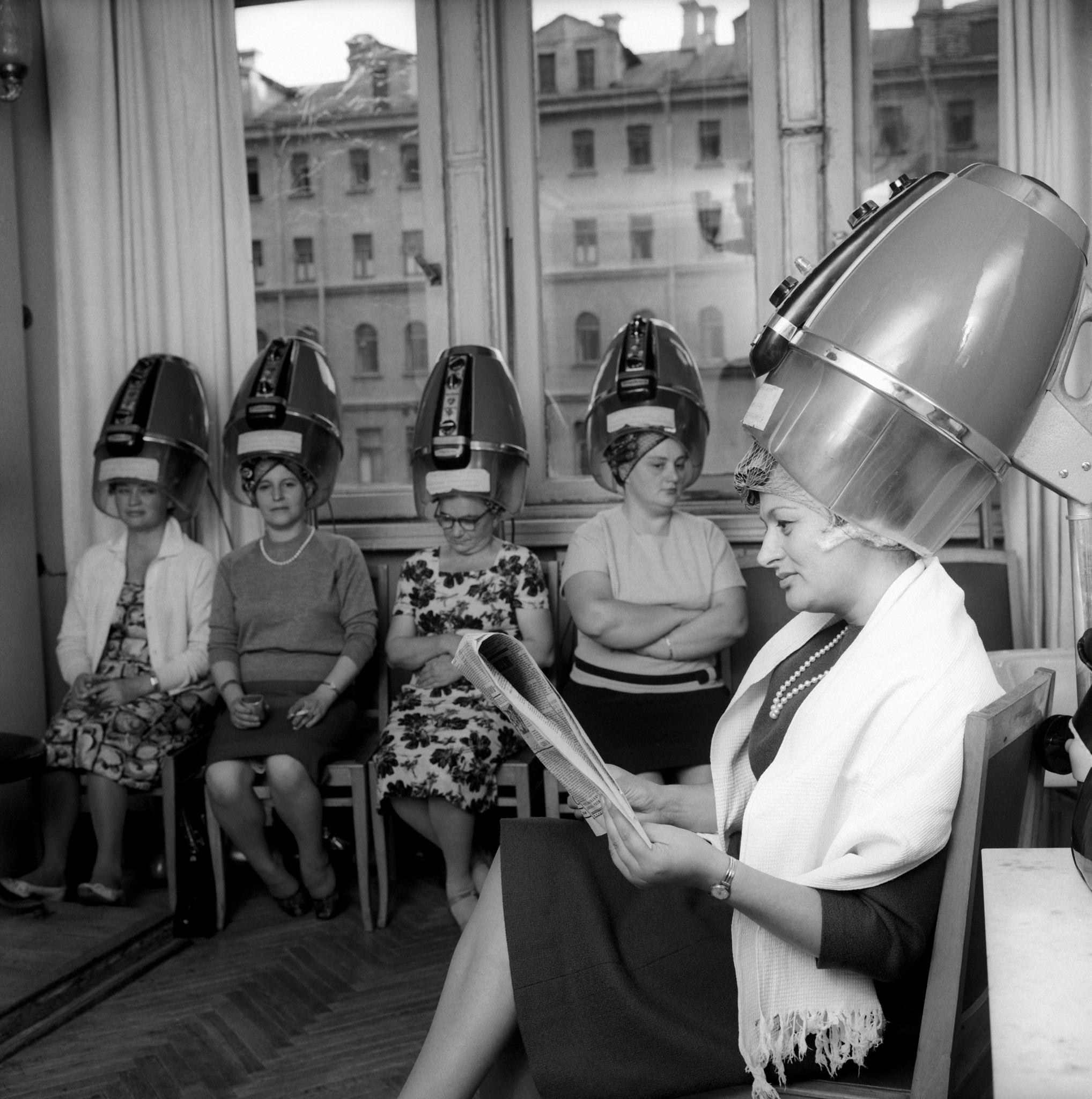 Эдда Винчензи у парикмахера; она села и читает русскую газету..png