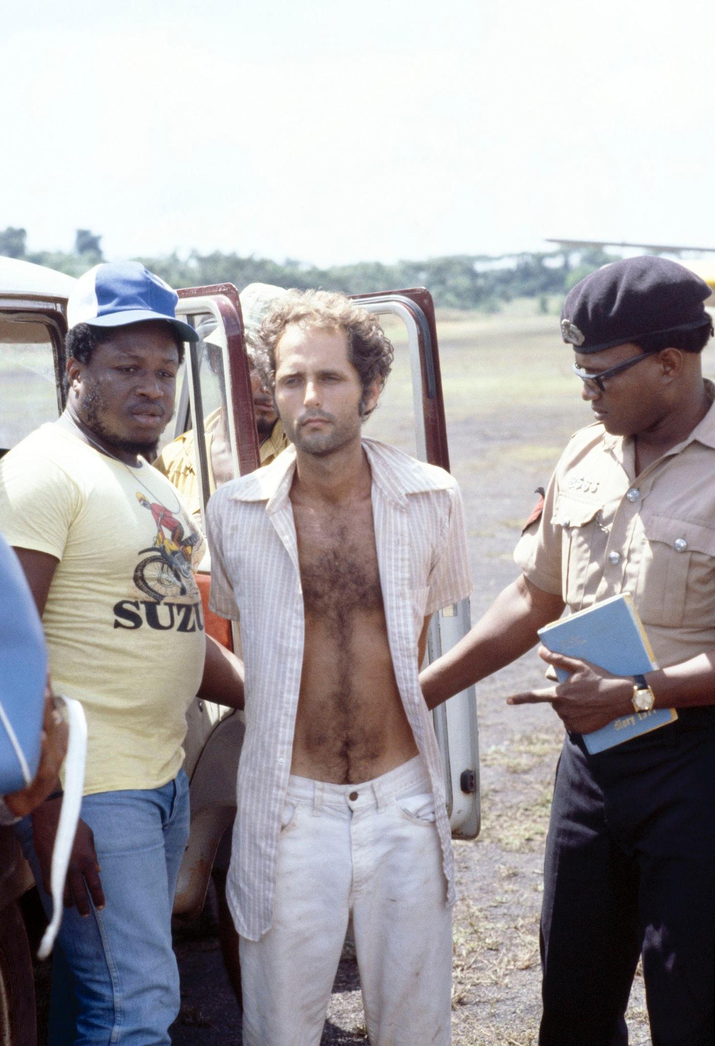 1978. Член секты Ларри Лейтон (С) стоит с полицией после ареста 18 ноября 1978 года, когда он стрелял в двух человек на удаленной взле…