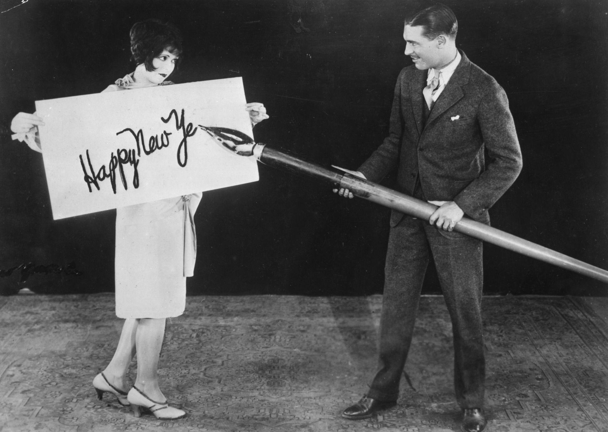 1925. Американская актриса Клара Боу держит большую карточку, а актер Ларри Грей надписывает новогоднее приветствие гигантской ручкой.jpg