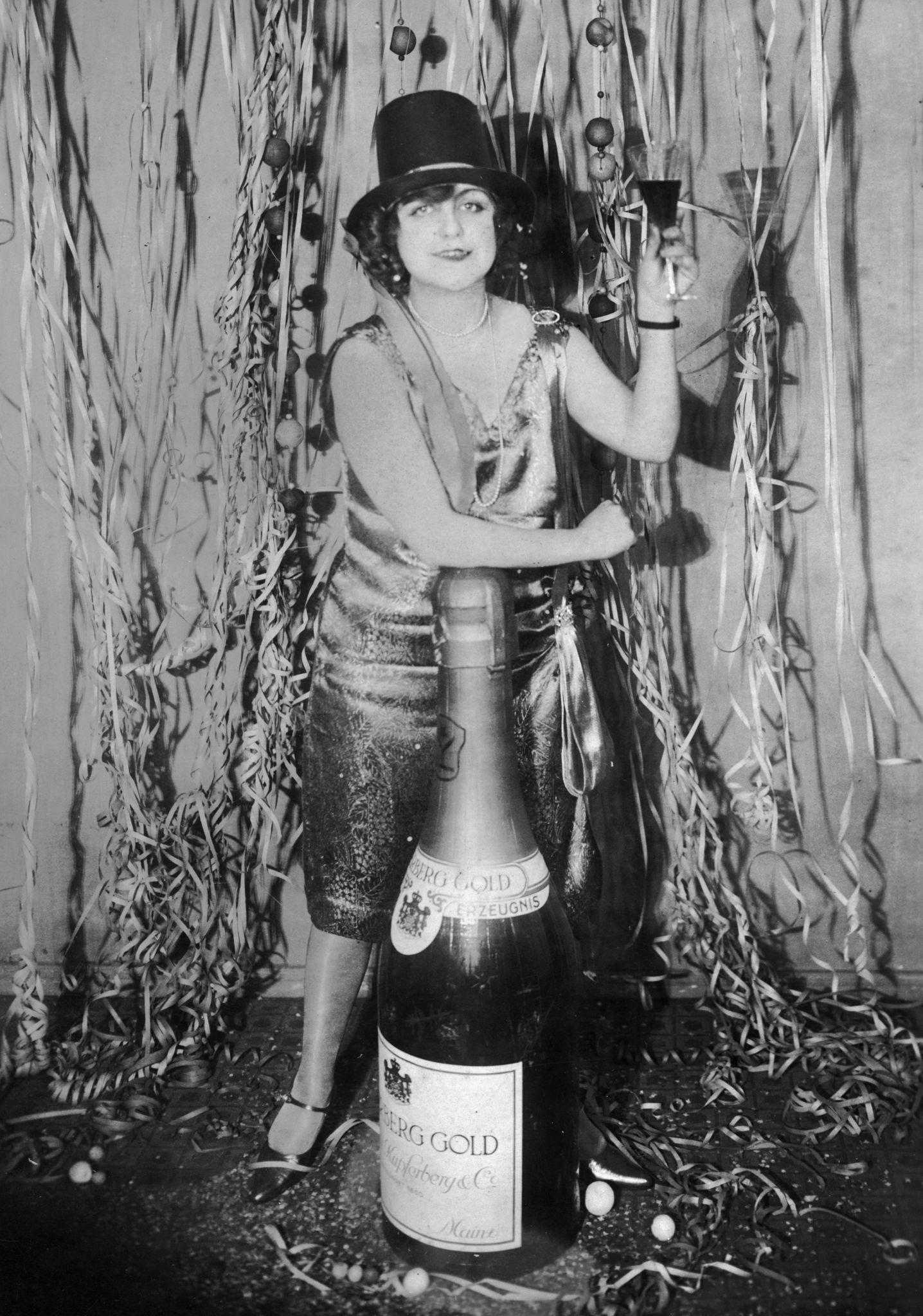 1925. Женщина на новогодней вечеринке опирается на бутылку шампанского большого размера., Германия.jpg
