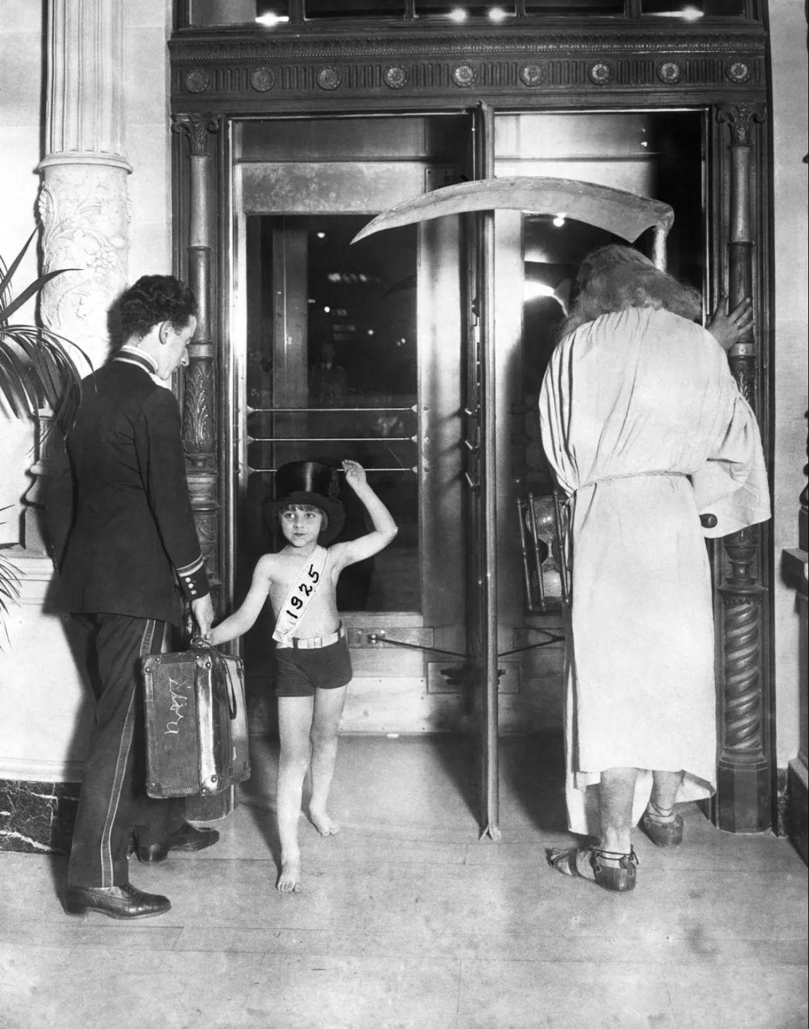 1925. Старый год (справа) уходит, так как новый год (как ребенок слева) проходит через вращающуюся дверь..jpg