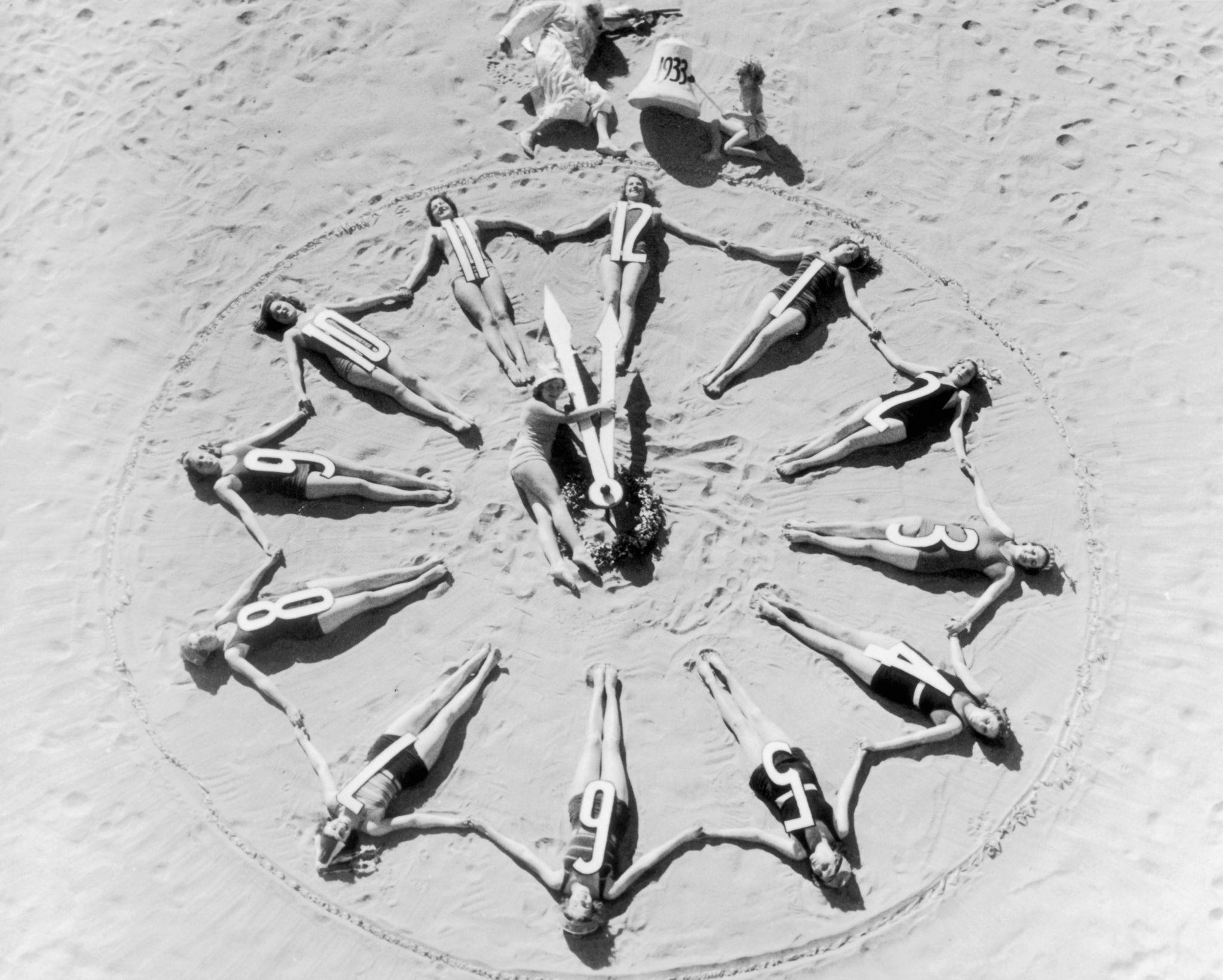 1932. Группа женщин и мужчина, одетый как Старый Отец, собирают гигантские часы из женщин на пляже, в канун Нового года. 31 декабря.jpg