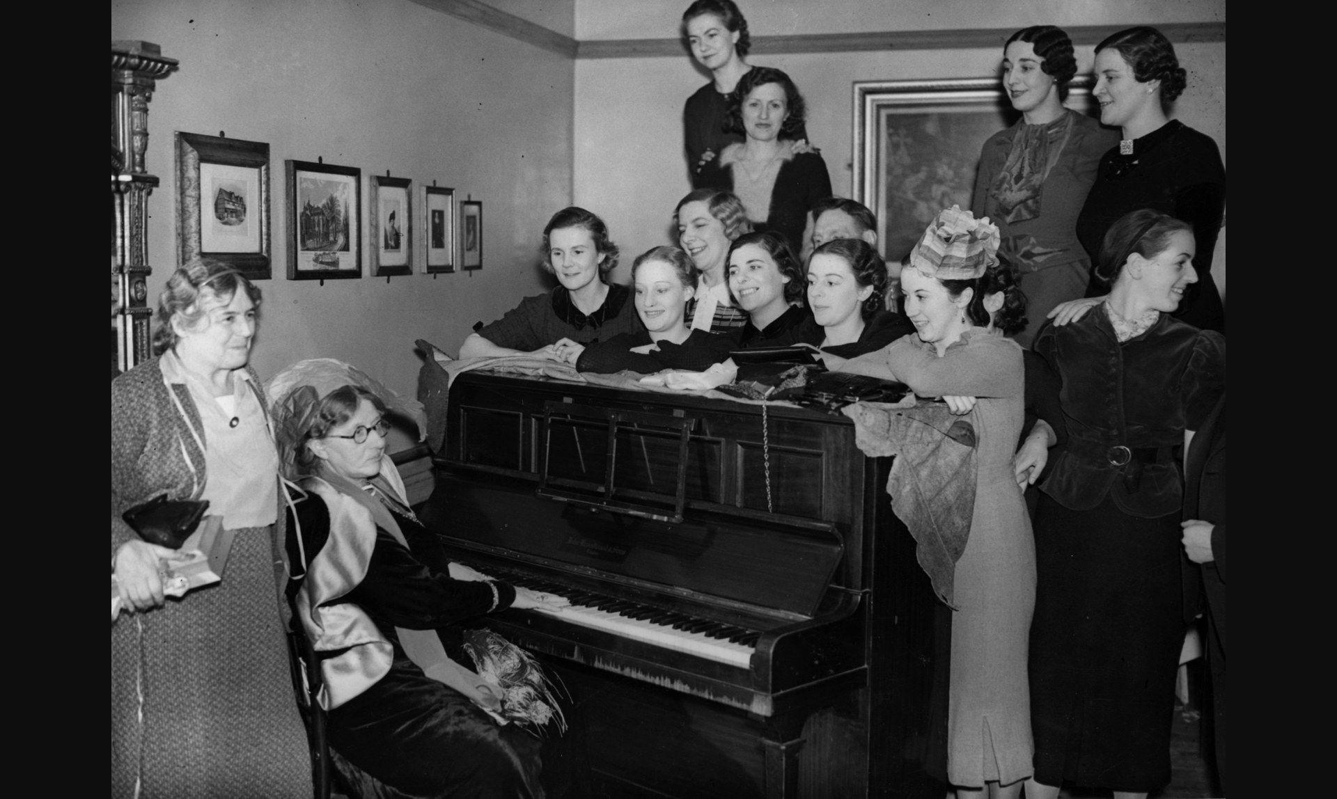 1937. Лилиан Бейлис играет на пианино на своей ежегодной новогодней вечеринке. Артисты балета собираются вокруг пианино для пения, 2 января.jpg