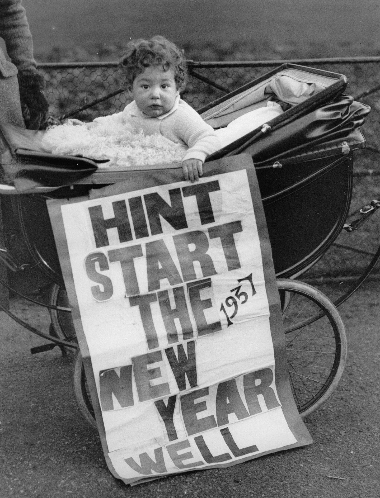 1937. Ребенок в своем багги 1 января держит плакат с полезными советами на новый год..jpg