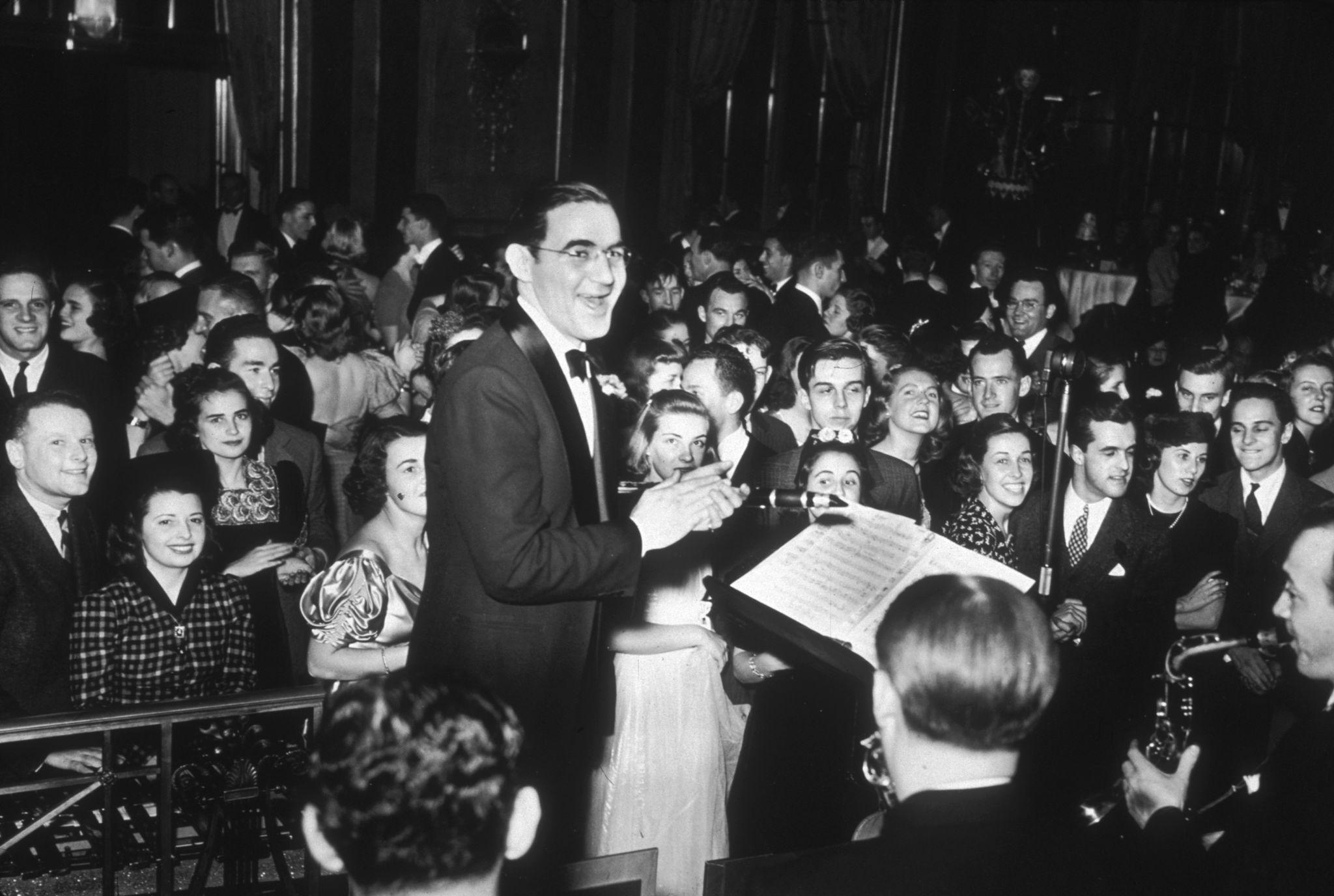 1938. Джазовый музыкант и руководитель группы Бенни Гудман и его оркестр играют для восторженной публики во время новогодней вечеринки в Waldorf Asto…