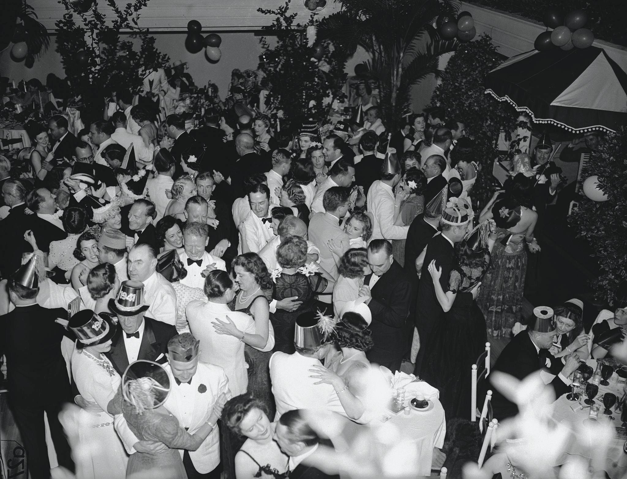 1940. Вид на танцпол в The Patio, где хорошо одетые пары (некоторые в праздничных колпаках) танцуют в канун Нового года, Палм-Бич, Флорида, 31 декабр…