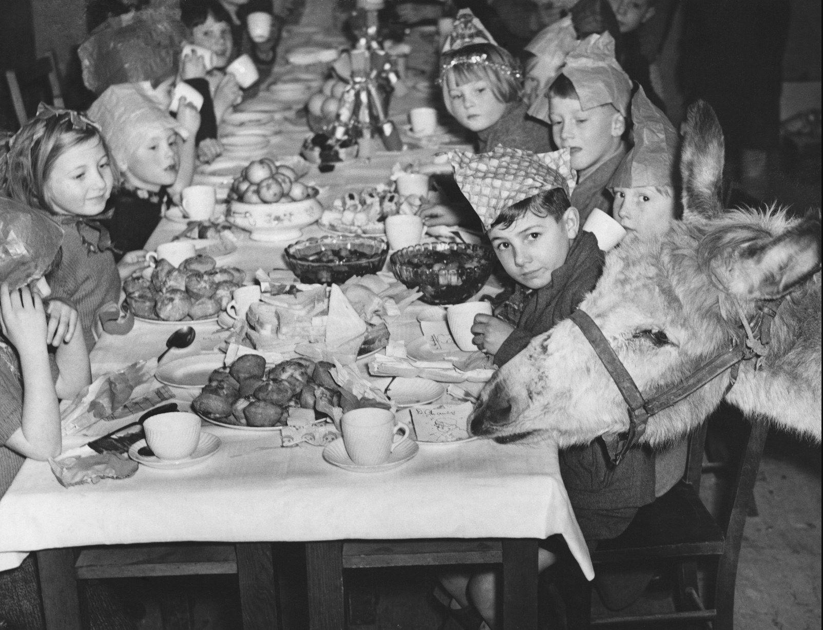 1940. Осел по имени Джако разбивает новогоднюю вечеринку, которую проводят дети, эвакуированные из Лондона в январе 1940.jpg