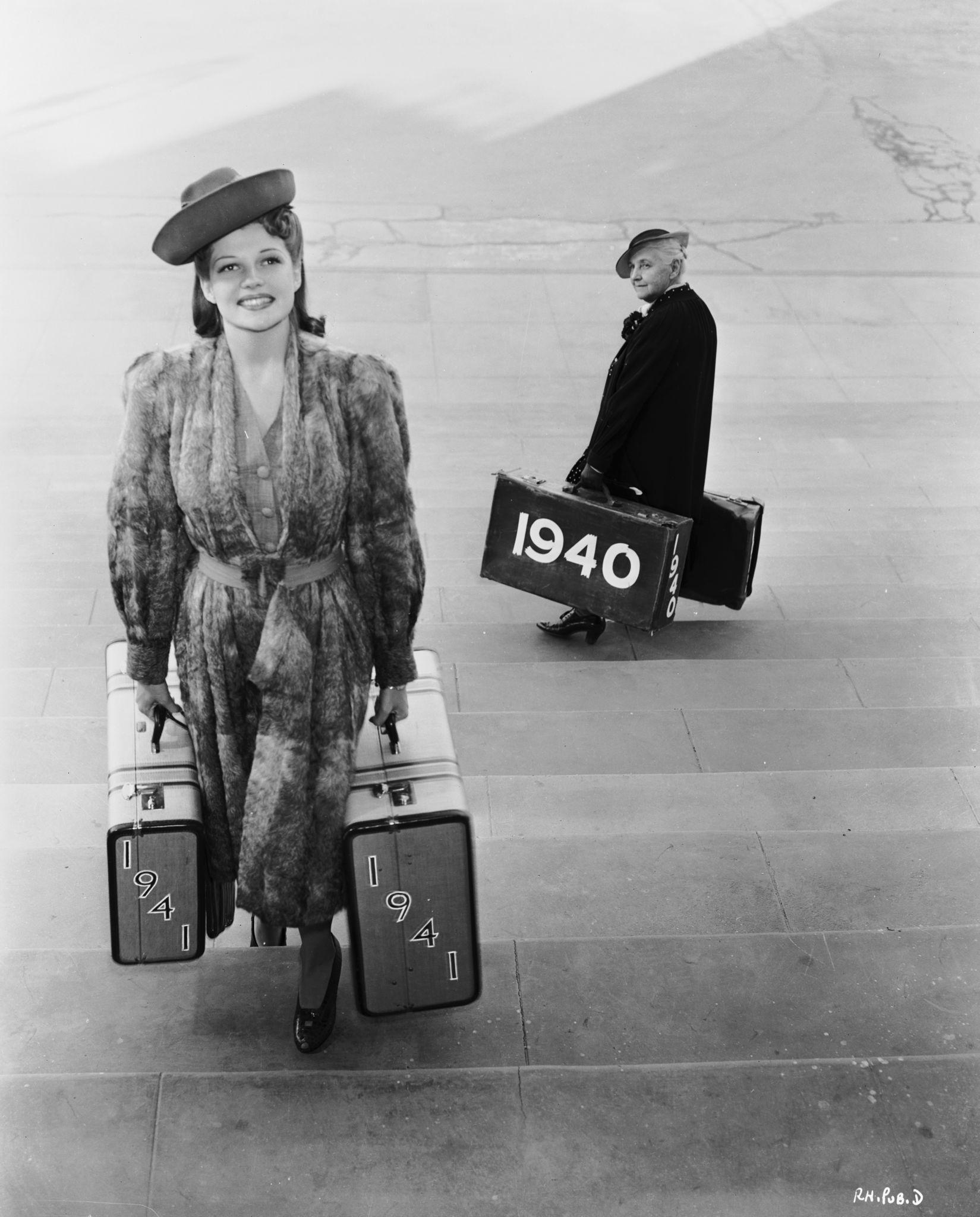 1941. Молодая Рита Хейворт, символизирующая Новый Год проходит мимо писателя Квентина Криспа в образе уходящего Старого года.jpg