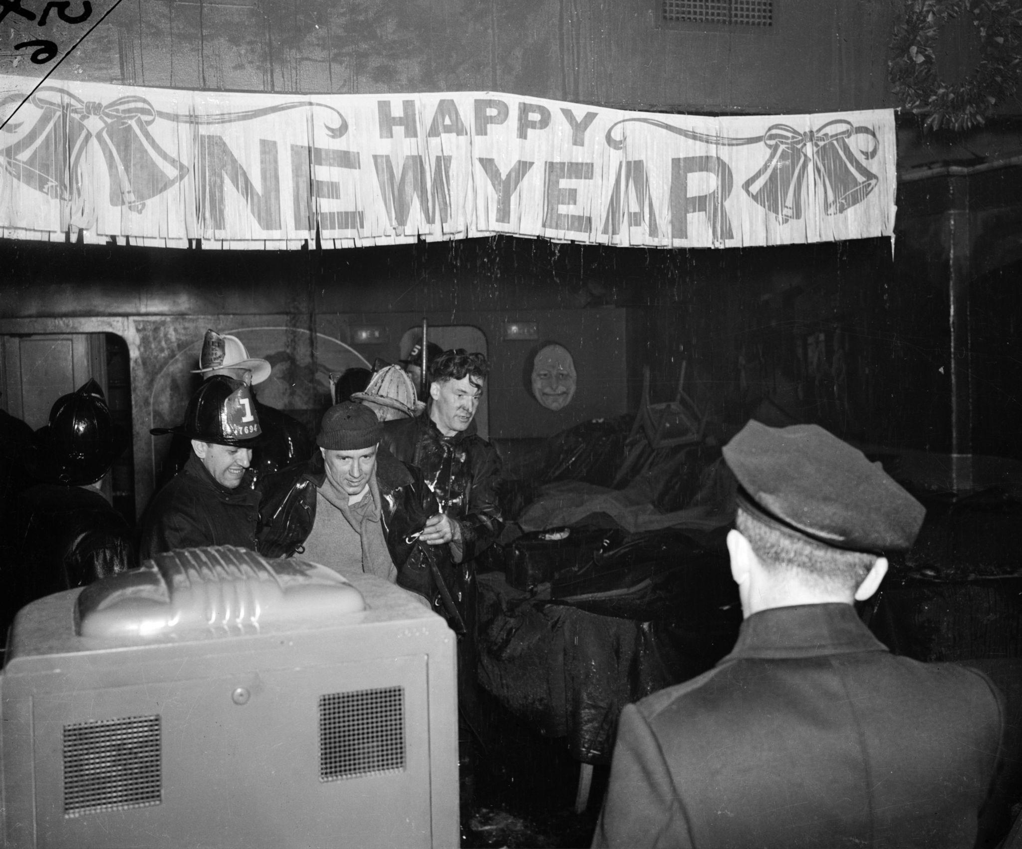 1941. Пожарные выводят мужчину из здания в Нью-Йорке, на котором висит плакат с надписью «С Новым годом».jpg